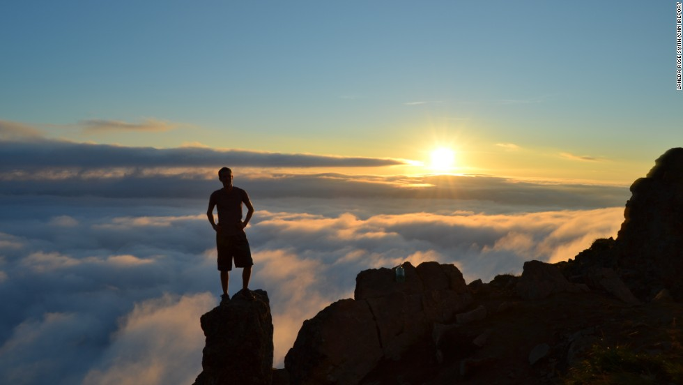 Shadowy figure of man standing on the top of a mountain top overlooking the sunset.