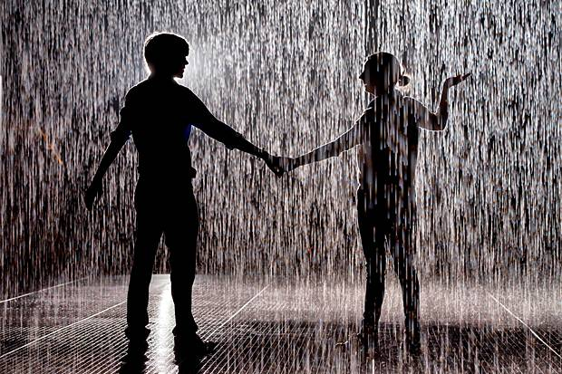 A young man and woman holding hands in the rain.