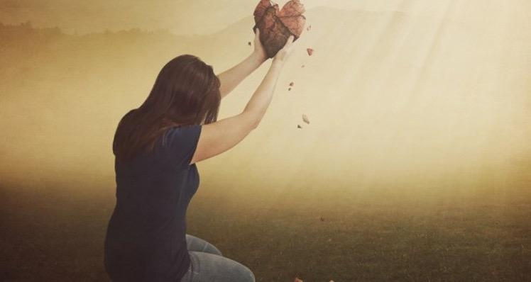 A woman raising up a broken heart is kneeling.