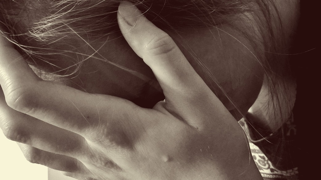 A woman weeping into her hands in prayer.