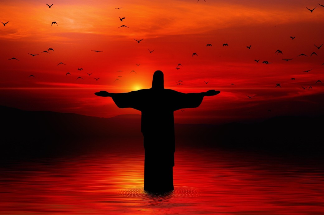 Shadowy figure of Christ standing on water with arms wide open and sunset and flocks of ducks to His back.