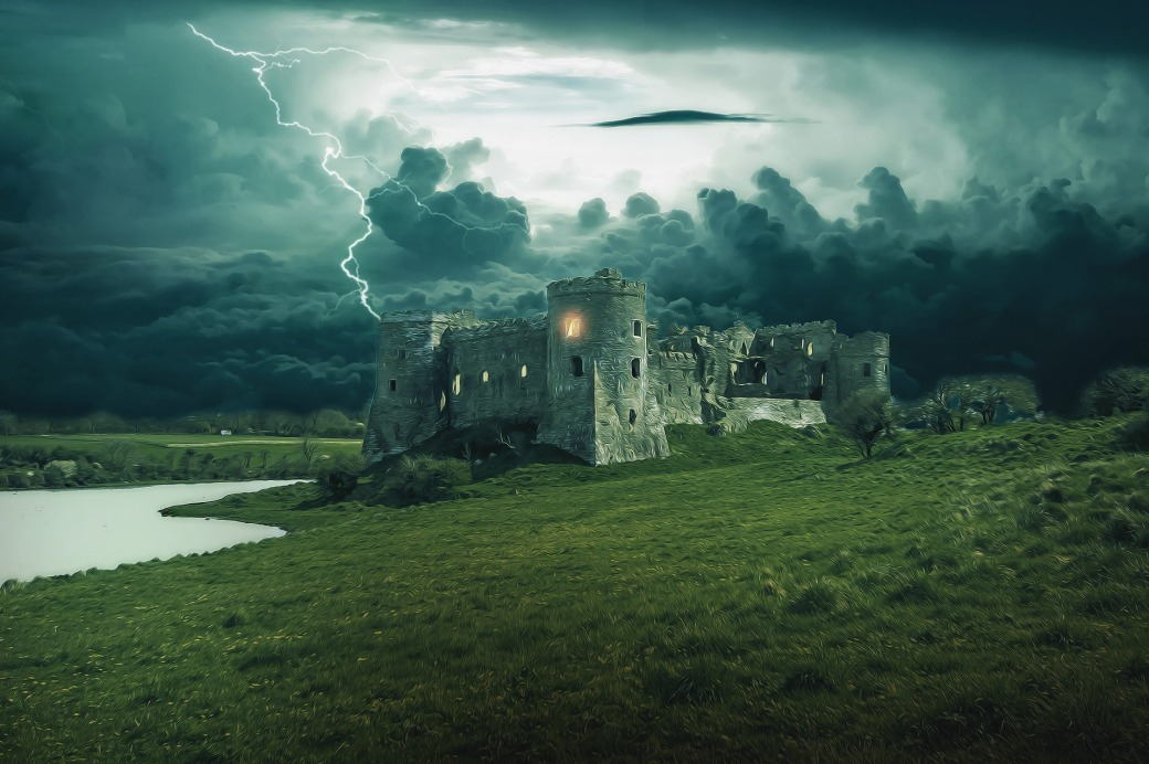Picture of a castle on a grassy hillside next to a stream with a light coming from a window in a front tower during a heavy storm.