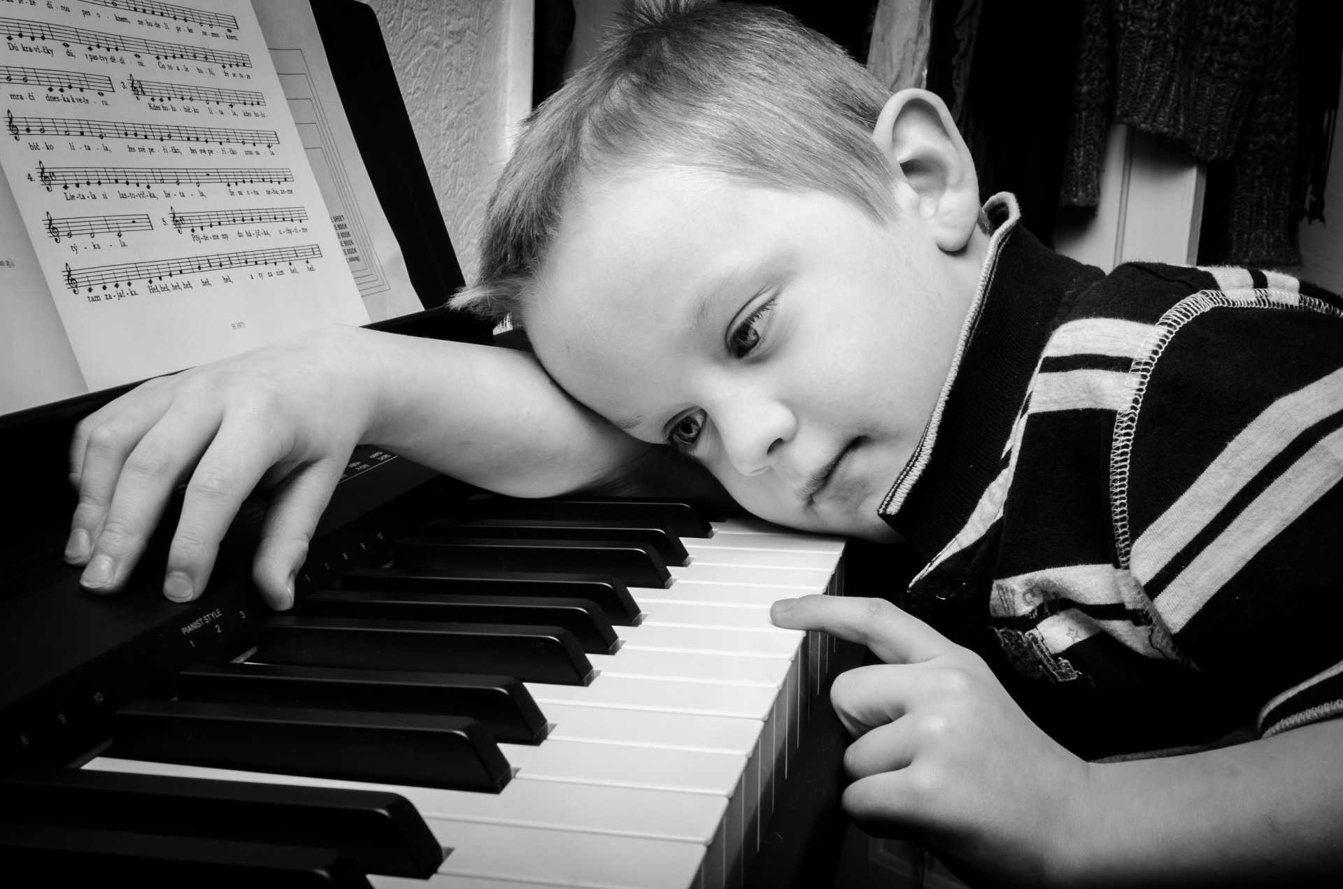 A boy lying over piano keyboard with finger on key.