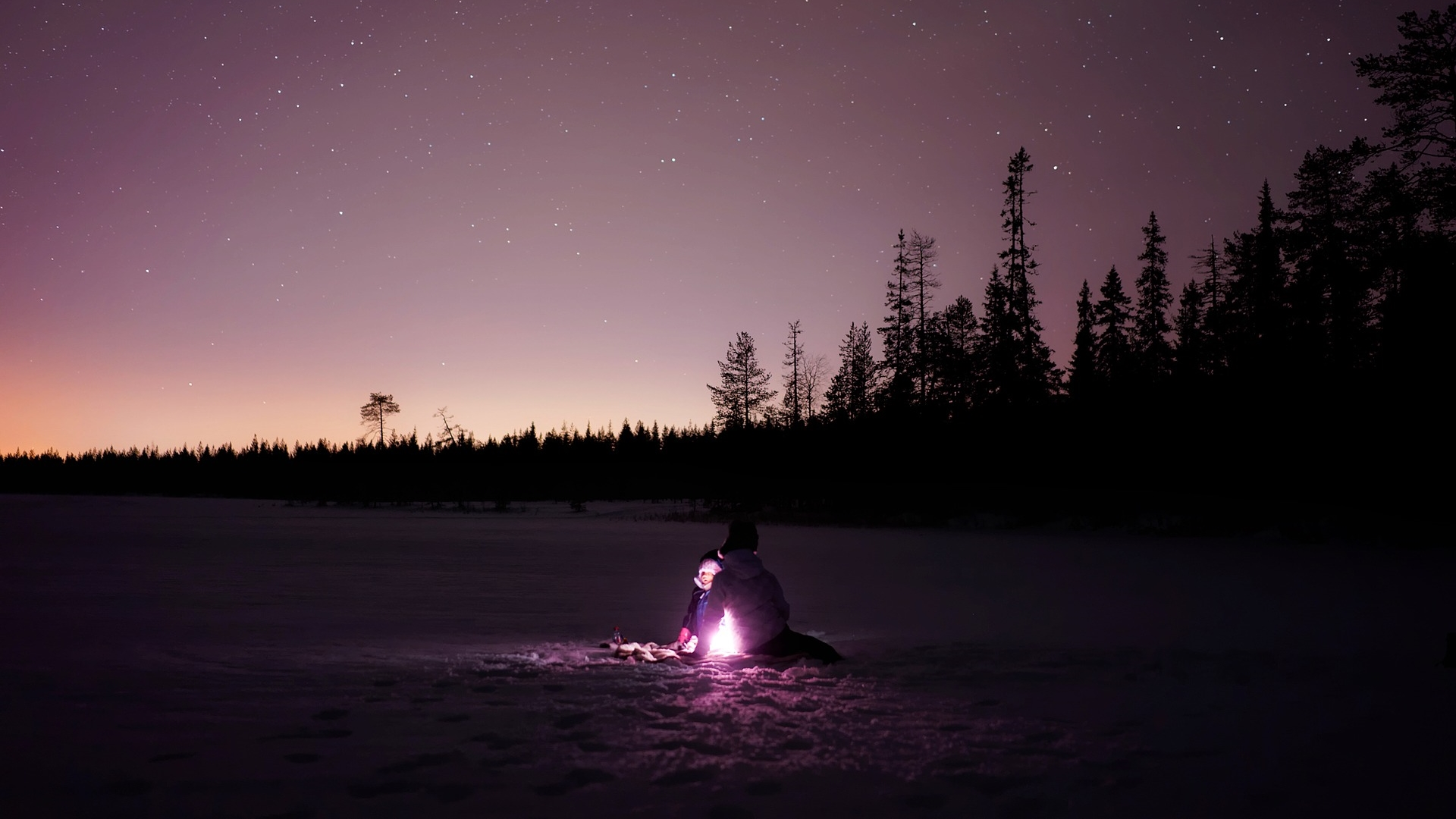 A campfire in the woods on a snowy night with a faint image of someone sitting next to it.
