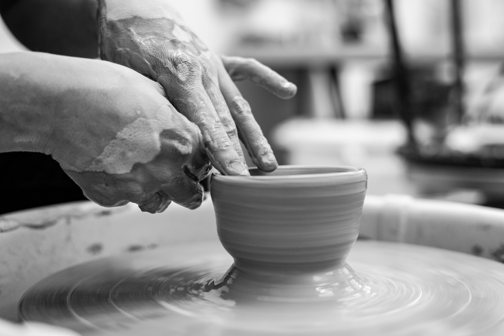 Black & white photo of a potter's hands as he fashions clay into a cup.